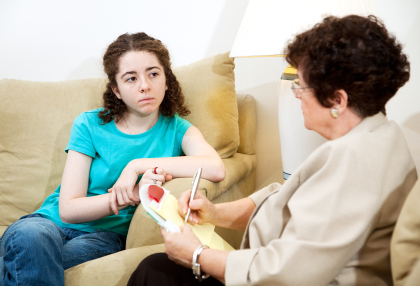 Depressed teen girl consulting with a psychologist.